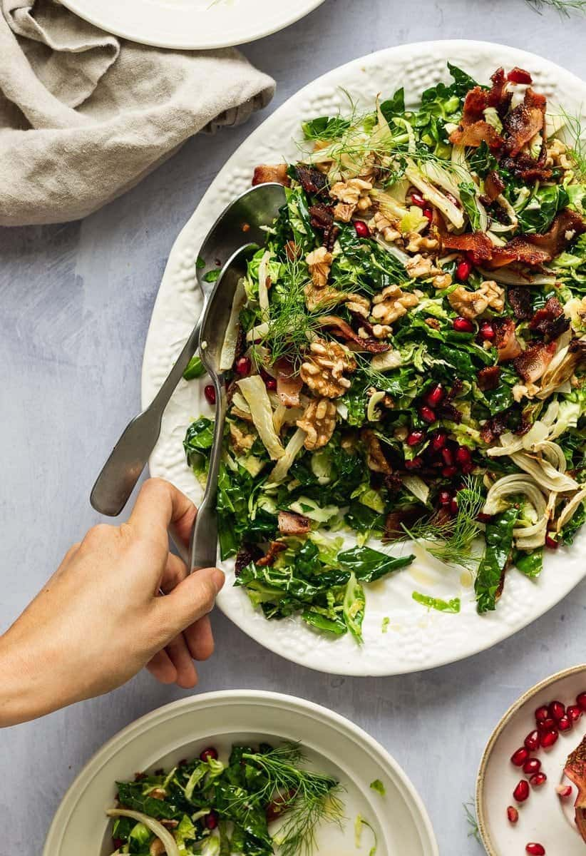 hand serving Brussels sprouts and kale salad