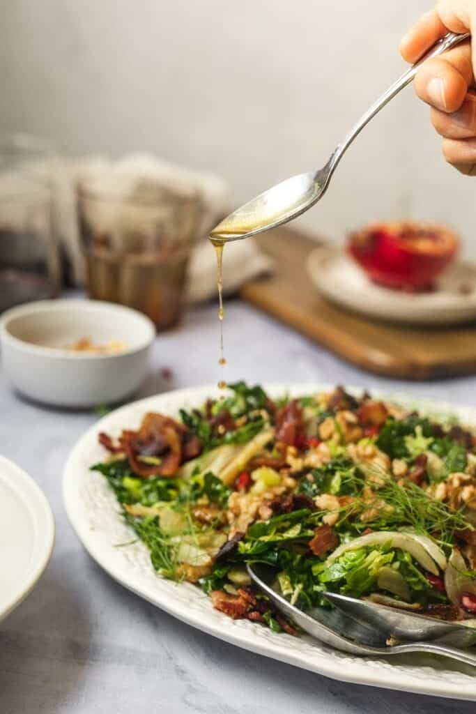 pouring maple bacon vinaigrette over Brussels sprouts and kale salad