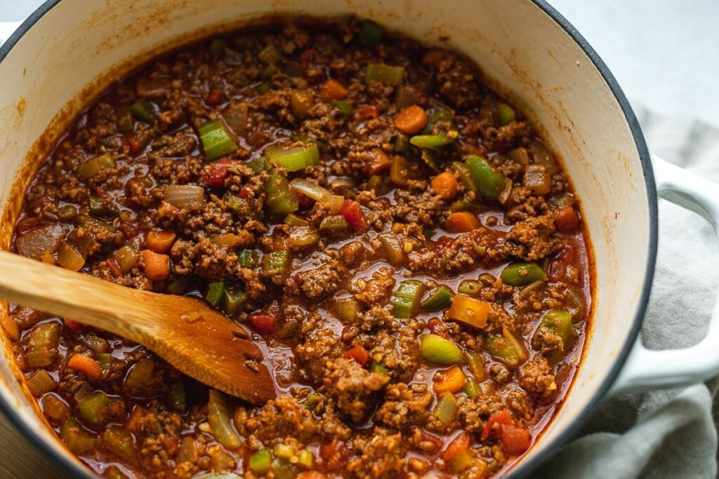 closeup of pot of keto chili with wooden spoon