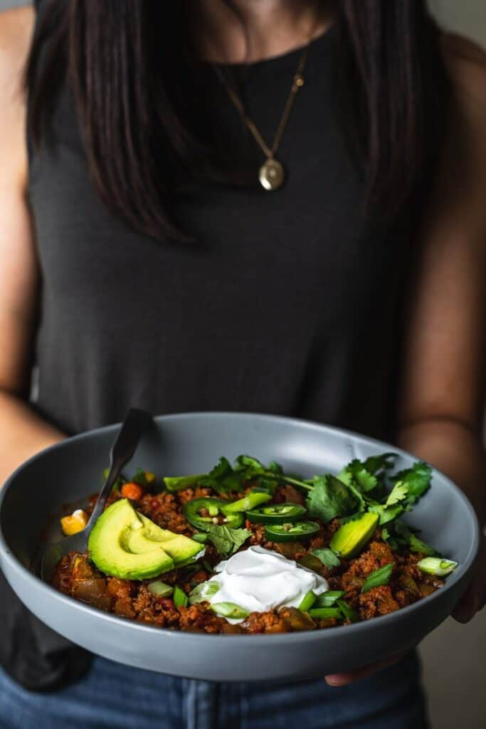 holding a bowl of keto chili with toppings