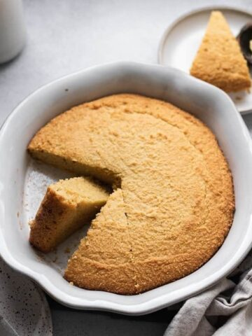 keto cornbread in baking dish with slice on plate