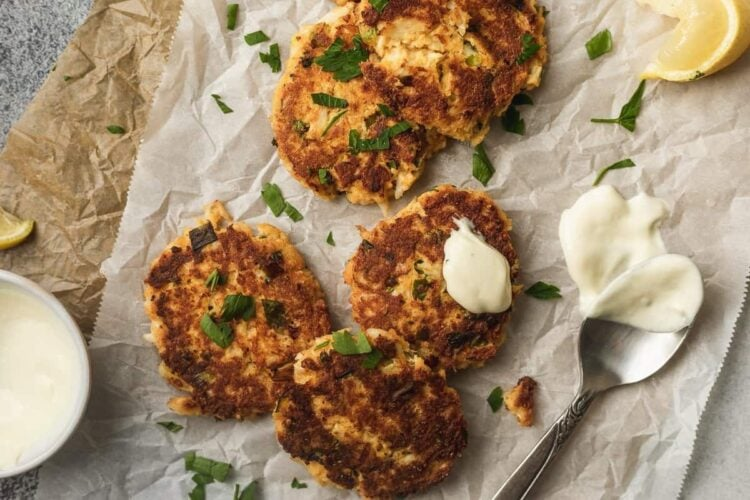 crab cakes on parchment paper with lemon aioli and spoon -horizontal