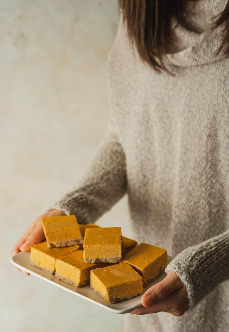 holding a plate of keto pumpkin cheesecake bars