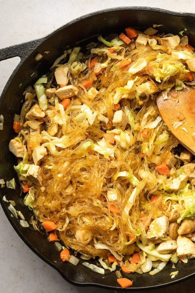 overhead of Filipino pancit in a cast iron skillet