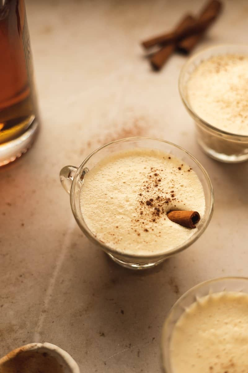 glass of keto eggnog with a cinnamon stick