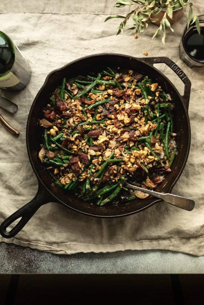 Keto green bean casserole in a cast iron skillet with walnut and bacon topping