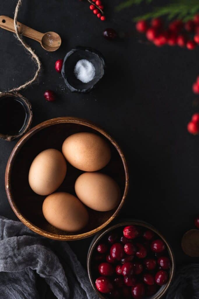eggs in a bowl and cranberries in a bowl for cranberry cake