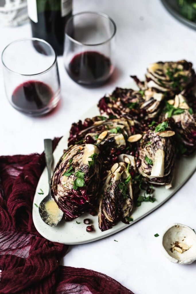 radicchio wedge salad on platter with dressing and wine glasses