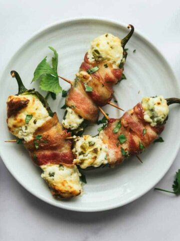 three bacon-wrapped jalapeño poppers on a plate
