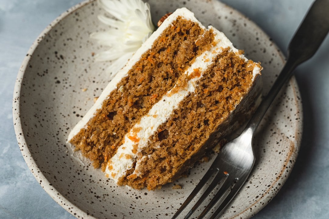 Slice of decorated keto carrot cake on a plate with a fork