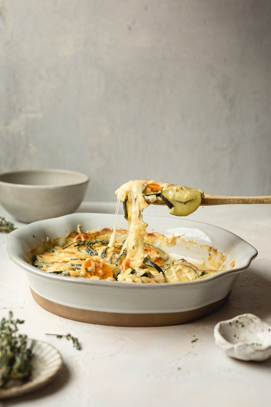 spoon pulling away a cheesy bite of zucchini gratin