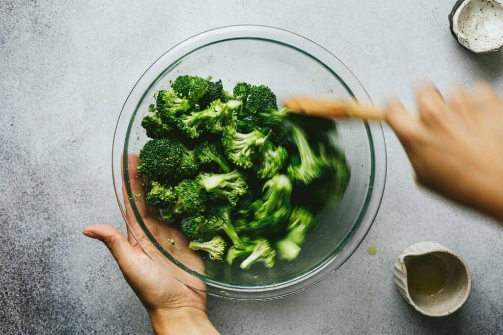 stirring broccoli in a bowl