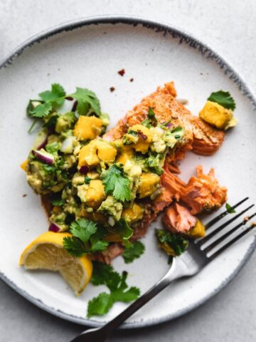 salmon with avocado salsa on a plate with a fork