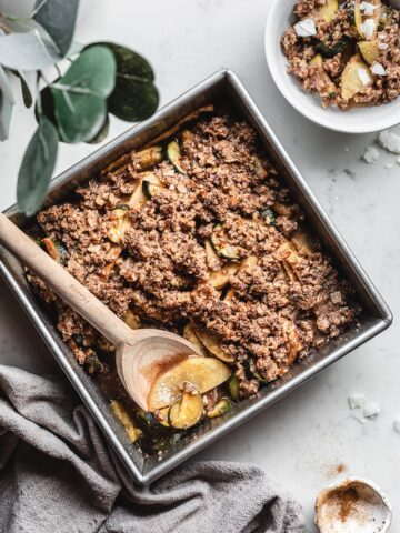 keto and gluten-free apple crisp in baking dish with napkin and wooden spoon