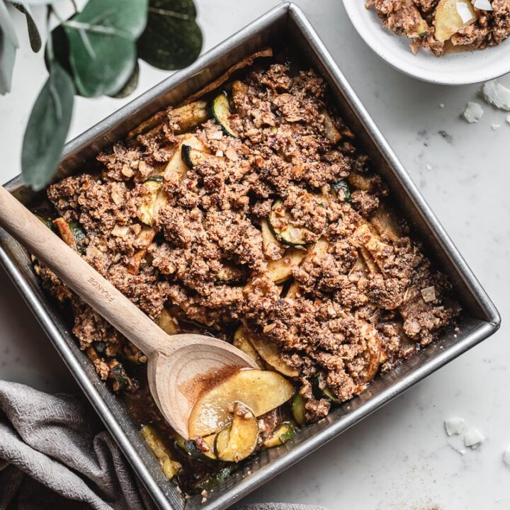 keto apple zucchini crisp with a wooden spoon in a baking pan