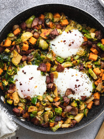 Brussels sprouts hash in a pan with a wooden spatula and cooked eggs on top