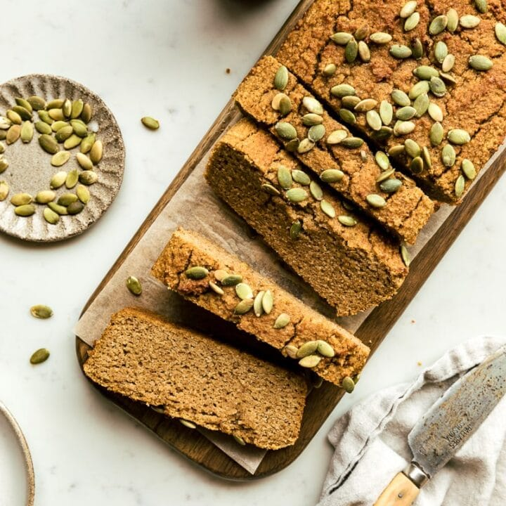 a loaf of healthy pumpkin bread with pepitas and coffee