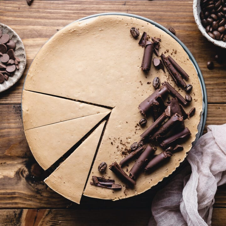 whole keto coffee cheesecake on a wooden table decorated with chocolate curls